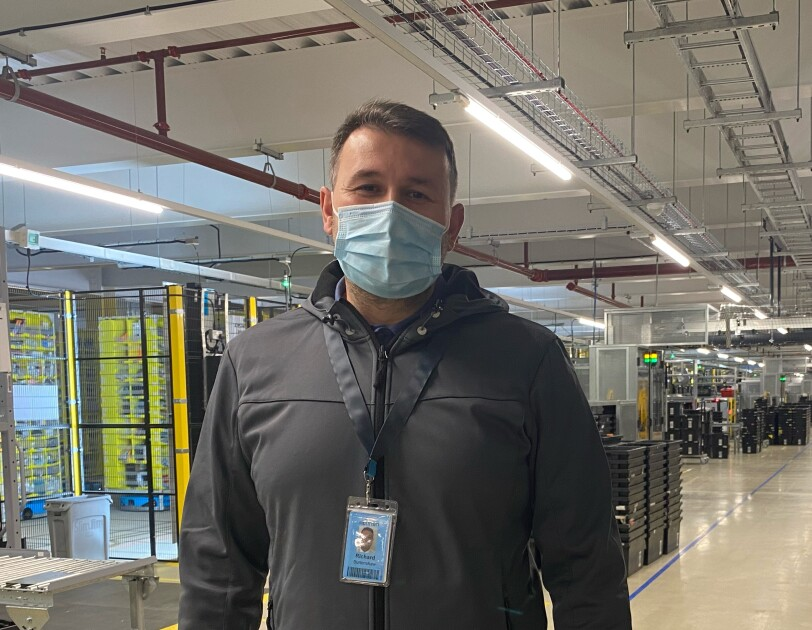 Richard Burtenshaw, FC Associate , he is wearing a face mask and standing in a fulfilment centre.