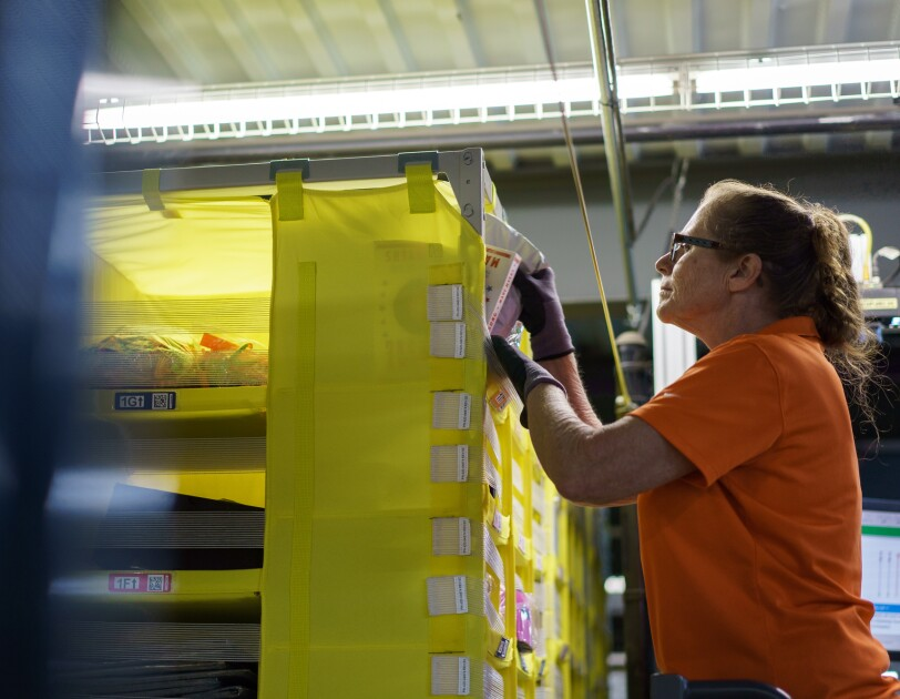 A woman wearing an orange T-shirt removes a product from a set of bins. She is wearing gloves and a pair of glasses.
