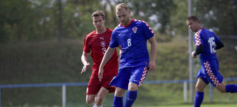 Zwei Fußballspieler auf einem Fußballfeld: Einer trägt ein rotes Trikot, der andere ist in blau. Beide springen hoch.