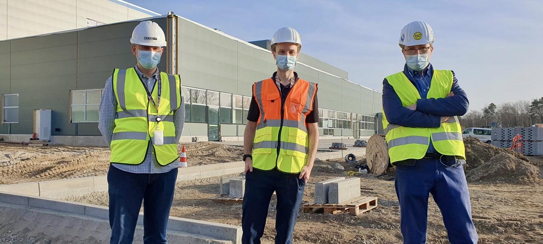 3 Männer in Helm, Sicherheitswesten und Masken vor dem neuen Amazon Logistikzentrum in Achim