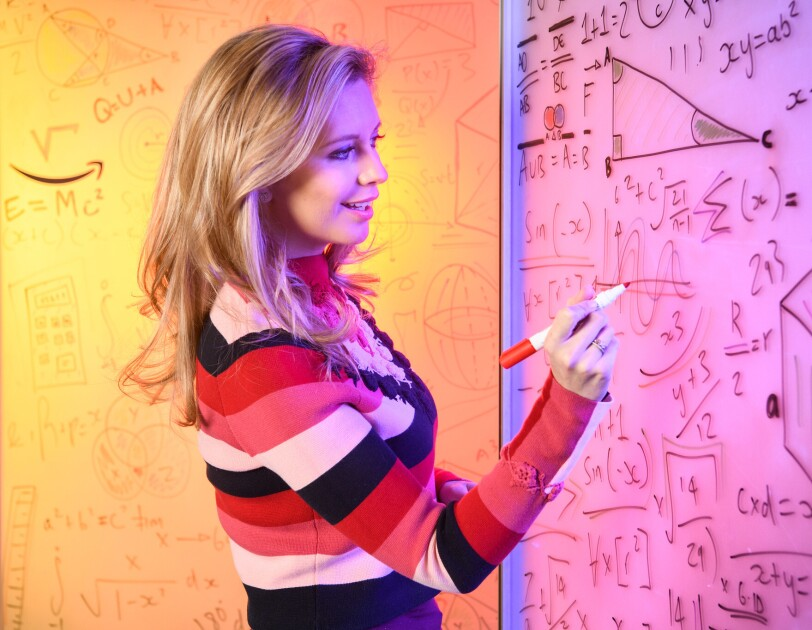 Rachel Riley writing maths equations and drawing graphs on a whiteboard.