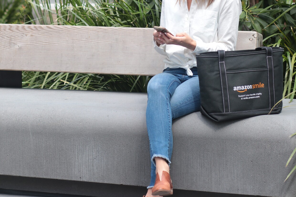 "A woman on a bench holds a smartphone. She is seated next to a tote bag with the AmazonSmile logo and the words ""Support your favorite charity at smile.amazon.com."""