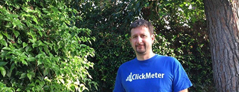 Ritratto a mezzo busto di Davide De Guz, sviluppatore di ClickMeter. L'uomo si trova in un giardino e indossa una t-shirt blu con il logo della sua azienda.
