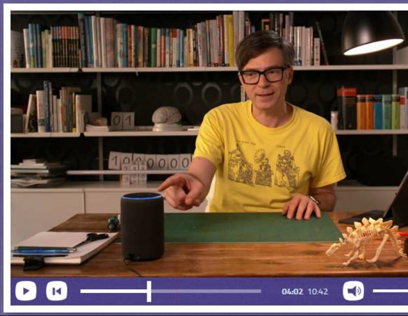 Ein Mann in einem gelben Tshirt sitzt an einem Schreibtisch und zeigt mit dem Finger auf  ein Alexa Echo.