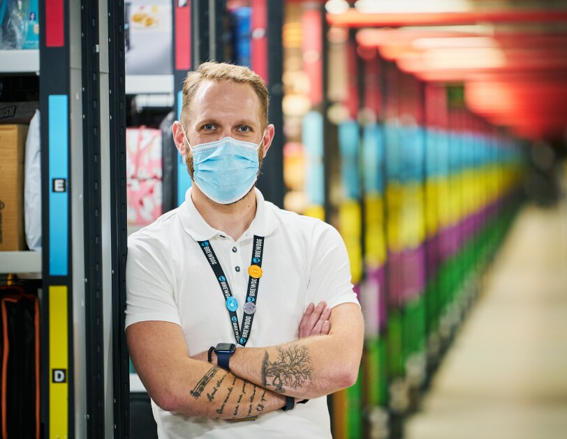 Craig Urquhart, Operations Manager at Amazon's fulfilment centre in Dunfermline, pictured cross-armed with colourful aisles blurred in the background