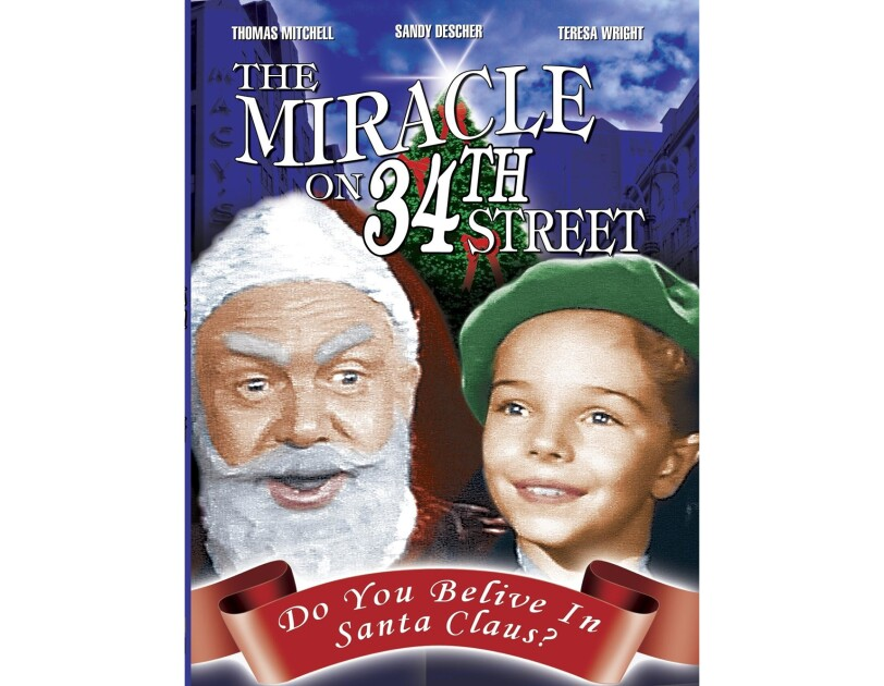 "Cover art for ""The Miracle on 34th Street"" shows a man dressed like santa, next to a young child in a green beret, with a Christmas tree behind them."