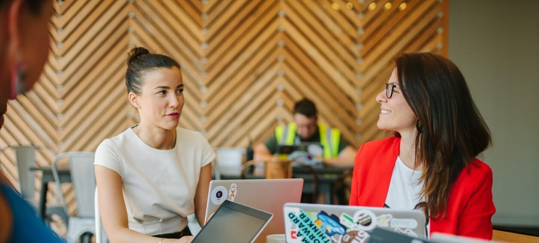 Drei Frauen sitzen am Schreibtisch, arbeiten zusammen und sprechen miteinander