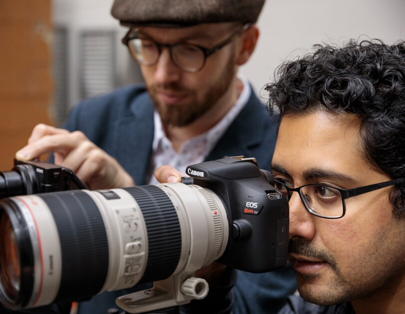 A man wearing eyeglasses uses a digital single-lens reflex camera equipped with a large professional lens. A second man is out of focus in the background.