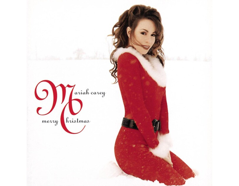 Mariah Carey wears a red dress with furry trim at the collar and cuff, and a thick, black belt. her outfit is reminscent of Santa's traditional Christmas look. She's kneeling on fresh snow, and looking to her left, at the camera. Behind her, in the distance are the hint of trees.