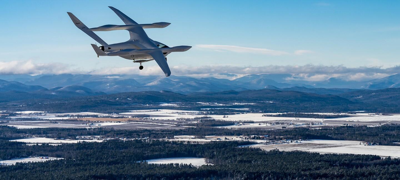 Ein klimaneutrales Flugzeug von BETA Technologies fliegt über einer Winterlandschaft.