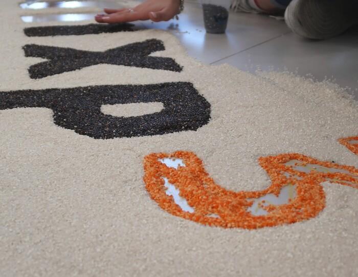 Dipendenti Amazon disegnano il logo MXP3 con il riso nero