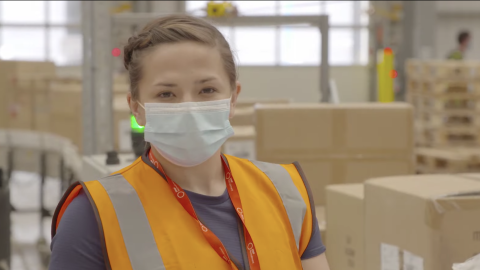 Amazon fulfilment centre employee wearing a face mask and orange hi-vis jacket.