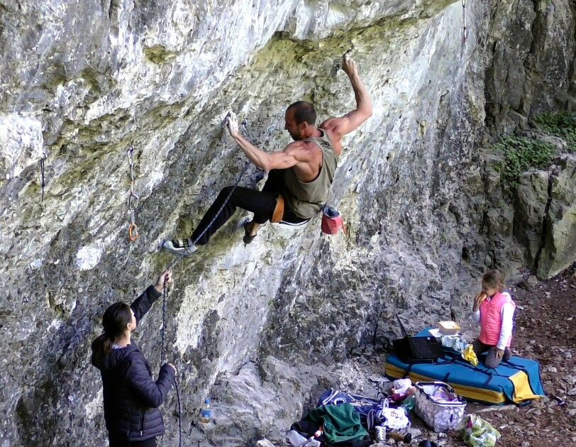 Ein Mann klettert an einer Steinwand und wird dabei von einer Frau gesichert.