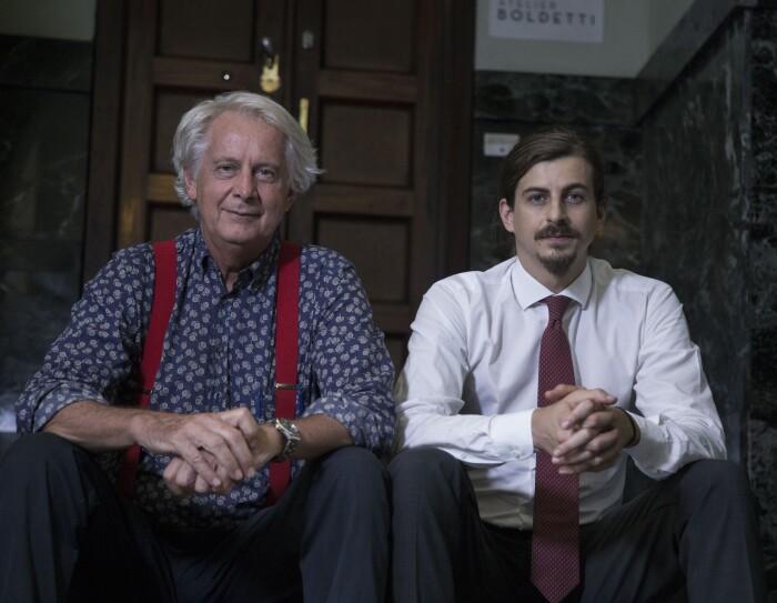 Due uomini sono seduti fianco a fianco su uno scalino all'ingresso di un palazzo. A sinistra Giorgio Boldetti, e accanto a lui Giulio Boldetti, 32 anni, entrambi proprietari dell'Atelier Boldetti di Torino.