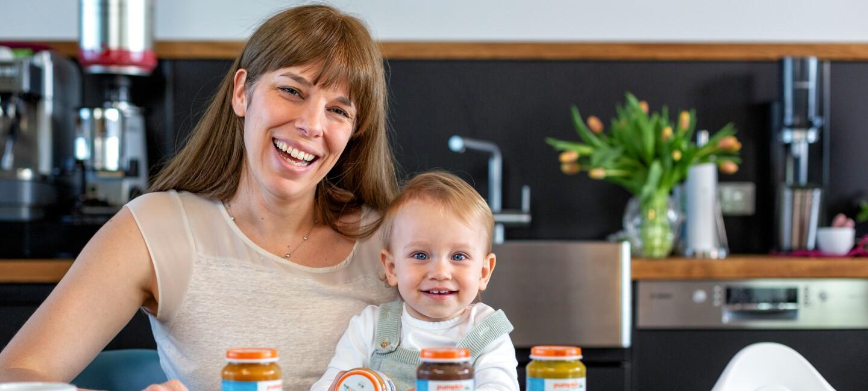 Eine Frau mit dunklen langen Haaren sitzt auf einem Stuhl. Auf ihrem Schoß sitz ein kleiens Kind mit blonden Haaren und einem Glas mit Babynahrung in der Hand.