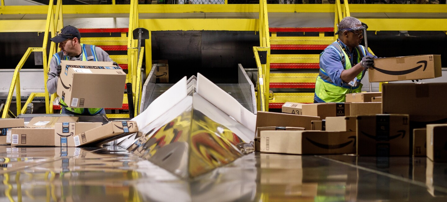 Two workers move cardboard boxes decorated with the Amazon smile logo.