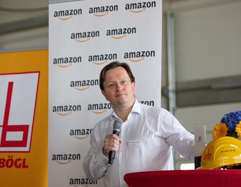 Ein Mann vor einem rot überzogener Stehtisch. Im Hintergrund sind Rollups mit Audruck amazon und Bögl zu sehen. Auf dem Tisch stehen ein gelber Bausstellenhelm sowie gelb-blaue Blumen