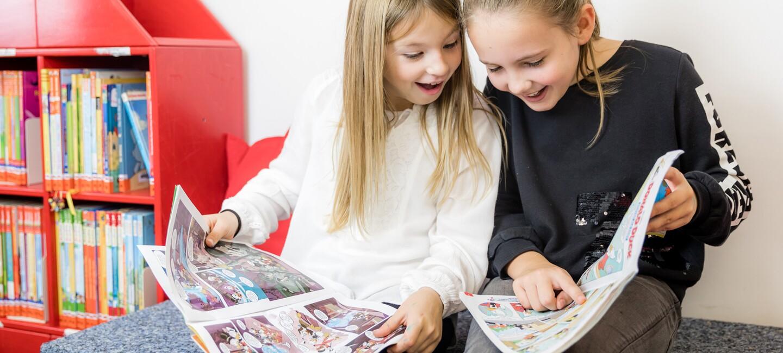 Zwei junge Mädchen lesen einen Comic.