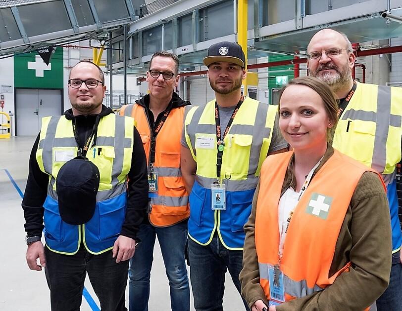 Vier männliche Mitarbeiter und eine Mitarbeiterin im Gruppenbild. Alle tragen Sicherheitswesten und lächeln in die Kamera