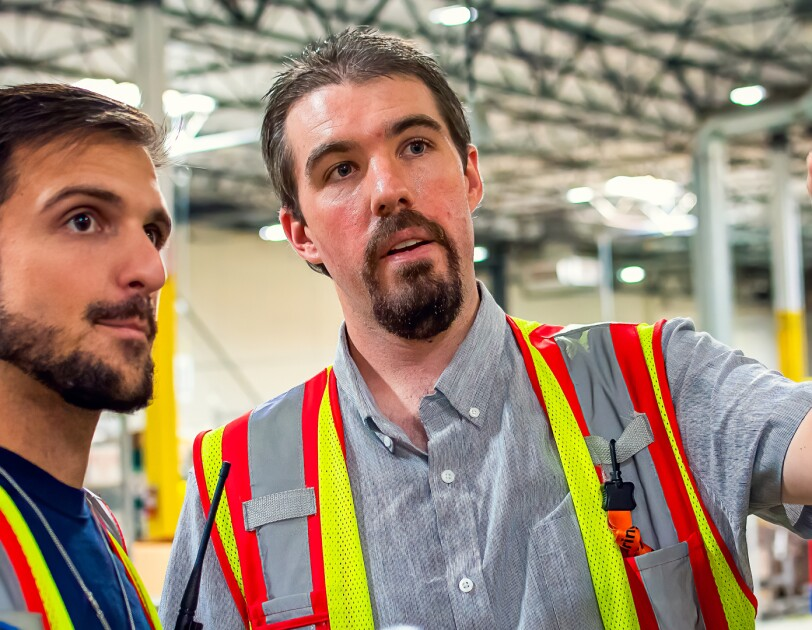 Two men in safety vests. One man gestures while the other looks on.