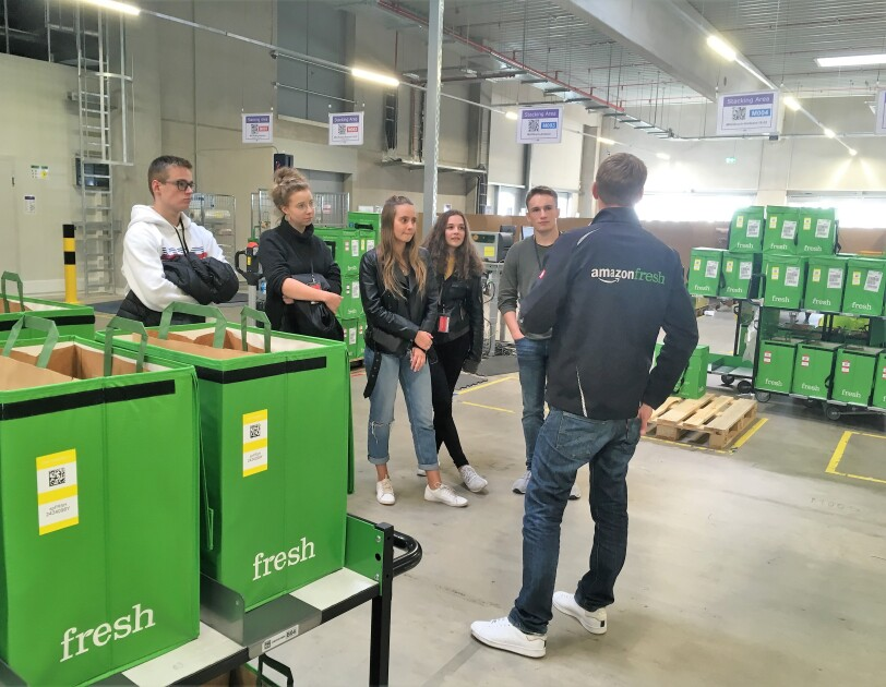 """Ein Fresh Mitarbeiter ist von hinten in einem Depot zu sehen. Überall stehen grüne Boxen, in denen sich die Bestellungen für die Kunden befinden. Er trägt eine schwarze Jacke mit Aufdruck """"Amazon Fresh"""". Vor ihm stehen die fünf jugendlichen Gewinner von """"Jugend gründet""""."""
