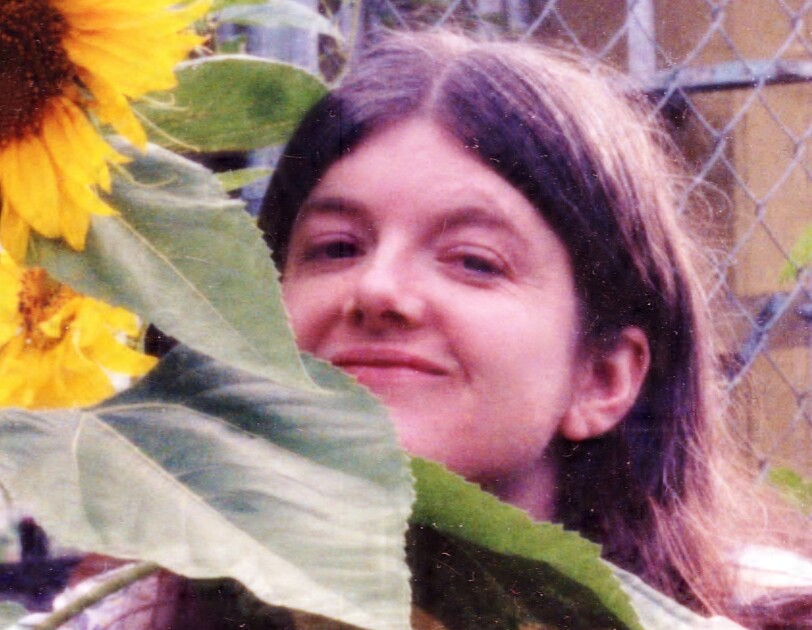 A vintage photo of author Jane Lotter, standing next to sunflower plant.