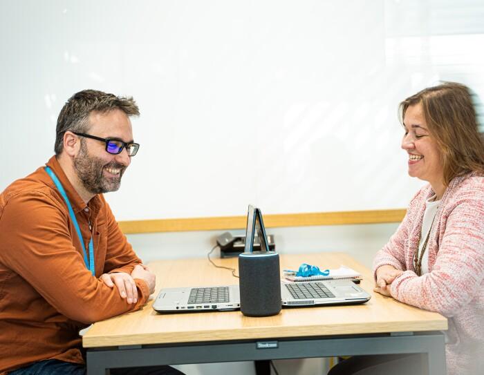 Marta Fernández y Daniel Méndez son Content Program Manager de Alexa. Se encuentran sentados de frende, en una mesa con dos ordenadores y un dispositivo Amazon Echo. Los dos sonrien mirando el dispositivo, tiene los brazos entrecruzados. Daniel con gafas de pasta negra, una camisa marrón y el pelo negro y blanco. Marta con una camiseta blanca y una chaqueta rosa.