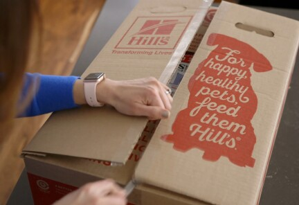 """A woman opens a recyclable Hill's Pet Food cardboard box that says, """"For happy, healthy pets, feed them Hill's."""""""
