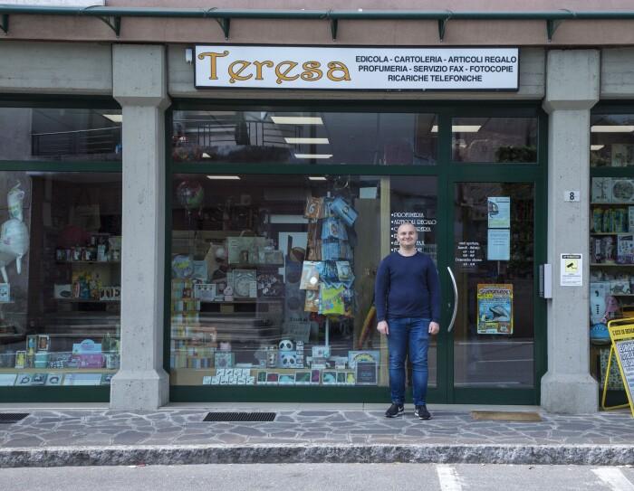 """Andrea Locatelli posa di fronte all'ingresso del negozio di Teresa. L'insegna dice """"Teresa - edicola, cartoleria, articoli regalo, profumeria, servizio fax, fotocopie, ricariche telefoniche."""""""