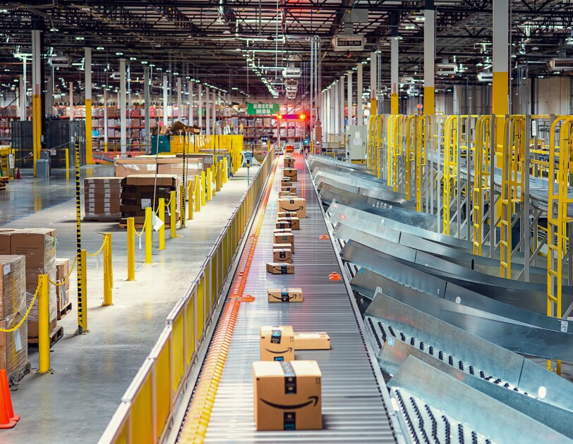 Boxes with the Amazon smile logo on a conveyor belt in a large warehouse space.