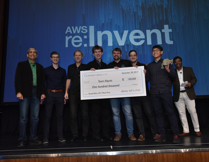 Amazon Alexa Prize winners from Team Alquist hold up a $100,000 prize check.