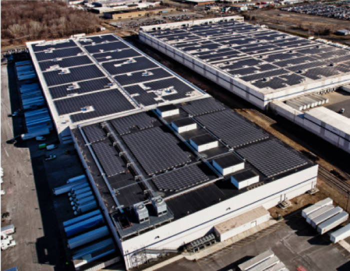 Aerial view of of two Amazon fulfilment facilities with solar systems on their rooftops.