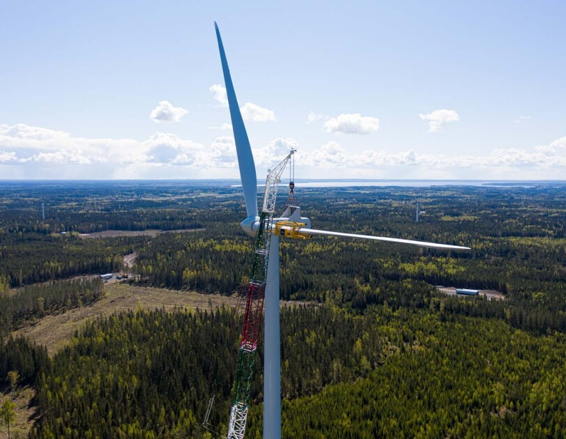 Aerial view photo of a crane assembling a wind turbine with the horizon as a backdrop, in Bäckhammar, Sweden.
