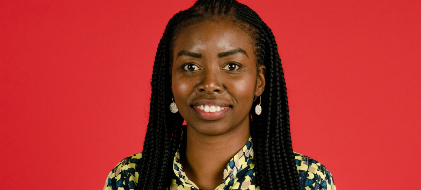 Headshot of Ramat Tejani in front of a bright red background.