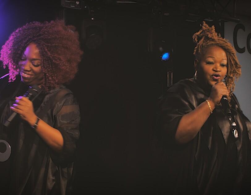 Zwei dunkelhäutige Sängerinnen stehen auf einer Bühne, in der Hand: Mikrofone