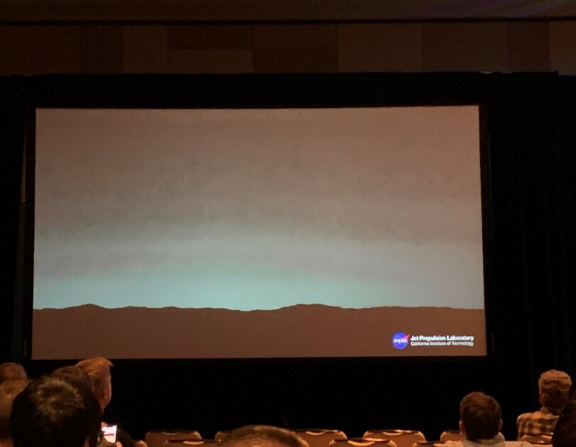A screen at a conference center, shows the view from Mars.