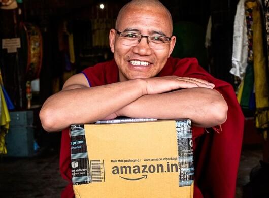 Monk smiling with Amazon box