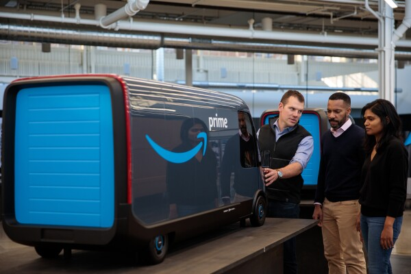 Three people look at a scale model of an electric delivery vehicle with the Amazon smile logo.