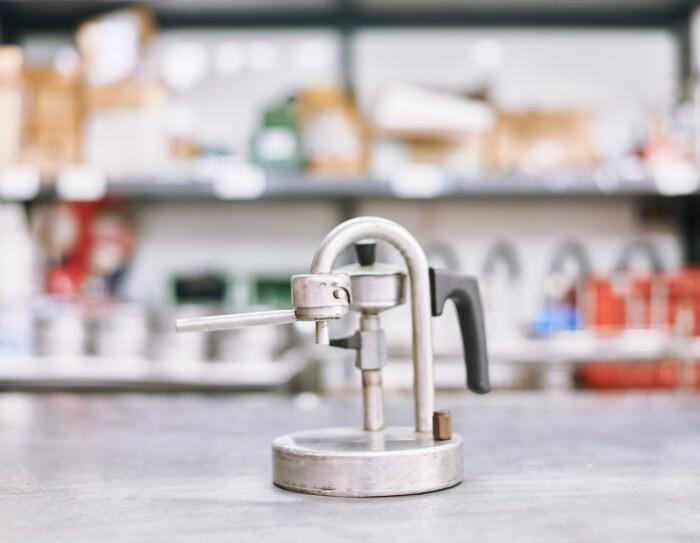 Foto di un prototipo molto essenziale di caffettiera Kamira. Manca quasi del tutto il serbatoio d'acqua, ma la linea a U invertita, il manico e l'erogatore si trovano già nella posizione che sarà quella della macchina finita.