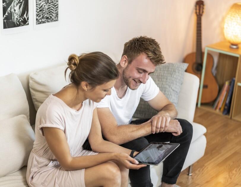 Ein junges Paar schmökert mit dem eReader
