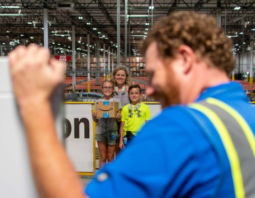 A man in the foreground triggers a camera to photograph a woman and two children standing with their backs to a vast warehouse space.