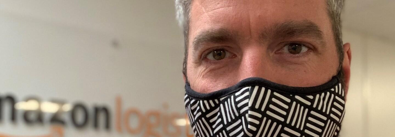 Amazon employee wearing  a mask and orange high vis vest