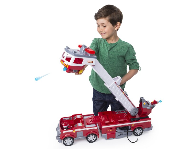 A Paw Patrol fire truck toy with a 2 ft. tall extendable ladder, mini fire cart, light and sounds, and water cannon launchers. A boy is kneeling behind the toy, exploring the features of the fire truck.