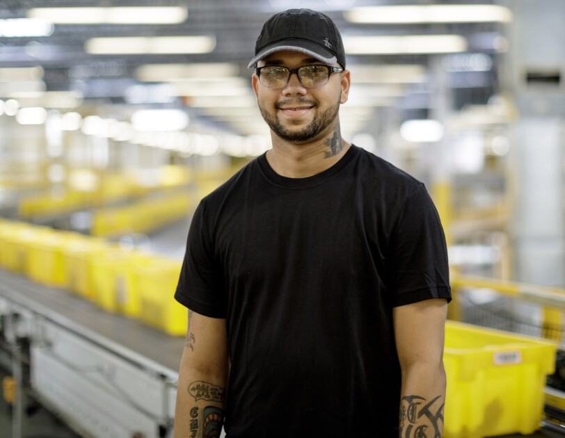 A man stands in a  large space flanked by a conveyor belt carrying yellow tote boxes. He wears glasses, a baseball cap, a black T-shirt, and work gloves.