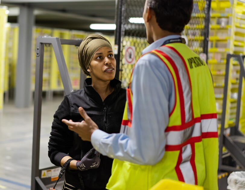 A woman and man talk in a warehouse. Yellow shelves of merchandise are in the background of the image.