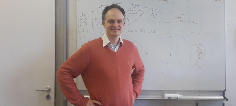 Ein Foto von Thomas Brox vor einer Tafel in einem Klassenzimmer