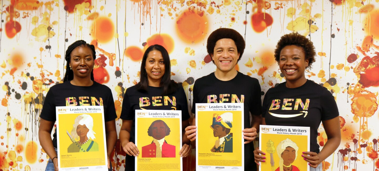 Picture of Amazon's Black Employee Network members holding posters of historic black figures (from left to right, Ramat Tejani with poster of Queen Nanny, Rebecca Wijeyesinghe with poster of Olaudah Equiano, Frederic Houinato with poster of Toussaint L'Ouverture and Aisha Suleiman with poster of Queen Amina)