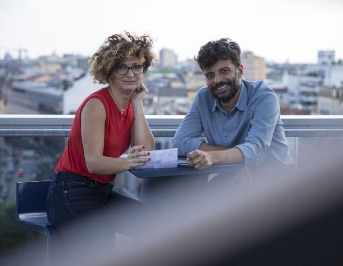 Due persone siedono allo stesso tavolo, sulla terrazza del palazzo Amazon di Milano. A destra, Alessandro Saccon, Consumer PR Manager. Di fronte a lui siede Alessandra Meucci, Executive Assistant. Sullo sfondo lo skyline di Milano. La foto è stata scattata in occasione del Pride di Milano di giugno 2018.