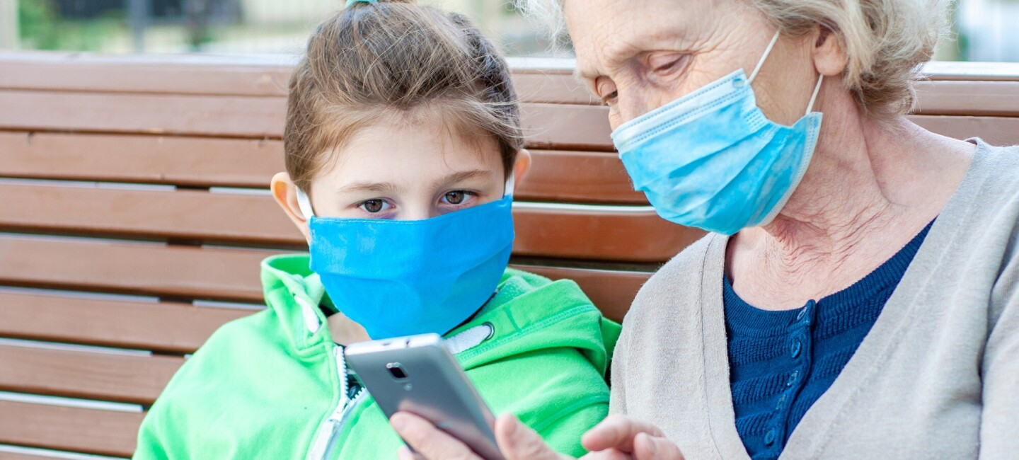 A grandmother is sitting with her grandchild on a bench. They are both wearing masks and looking at the grandmother's phone.