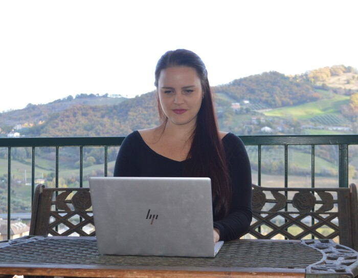 Una donna è seduta ad un tavolo su un terrazzo e ha di fronte a sè un PC. Alle sue spalle delle colline.
